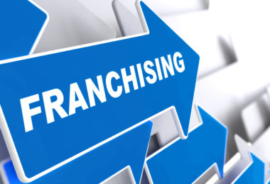 "Franchising - Business Background. Blue Arrow with ""Franchising"" Slogan on a Grey Background. 3D Render."